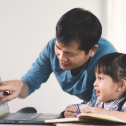 parent teaching his child to navigate learning platforms in a private school